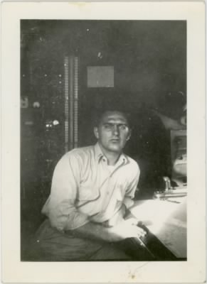 "William E. Prettyman at work on his navigator's table.  On the back of the photo, his caption reads ""note the ceegar!"""